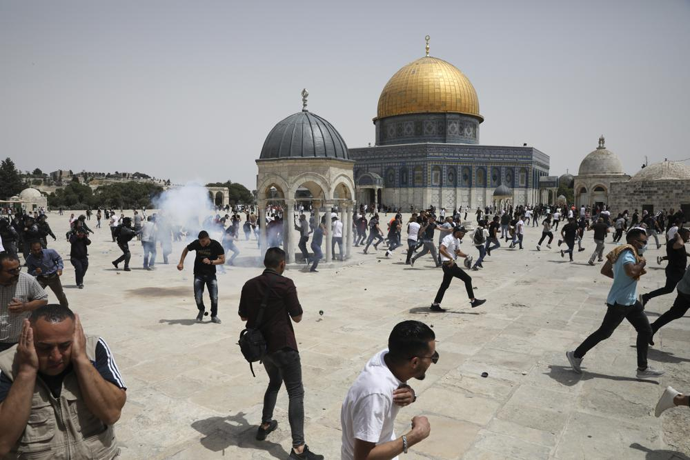 Palestinians run from sound bombs thrown by Israeli police in front of the Dome of the Rock shrine at al-Aqsa mosque complex in Jerusalem, Friday, May 21, 202, as aa cease-fire took effect between Hamas and Israel after 11-day war. (AP Photo/Mahmoud Illean)